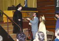 An unidentified woman (L) whom just received her diploma in an audience is about to shake hands with a unidentified man (M) who is holding his hand out towards her in Otto Arena, Mankato State University