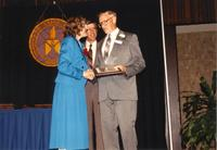 Winton Benson shaking hands with Margaret Preska after receiving an award at Retirement Banquet located in the Centennial Student Union. Mankato State University, June 1, 1989.