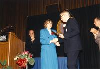 Male shaking hands with Margaret Preska at retirement banquet located in the Centennial Student Union. Mankato State University, June 1, 1989.