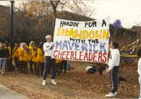 MSU's cheer squads stunt men holding a banner to cheer on the cheer squad for Homecoming, Mankato State University