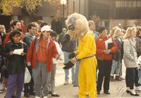 A group of students and faculty standing outside of Armstrong Hall and Wigley Administration Center with Stomper in the middle, Mankato State University.