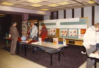 "A group of unidentified men and women standing behind a table informing others about the ""Teaching about the Soviet Union and Global Education in the Partnership Schools in the Centennial Student Union, Mankato State University."