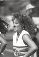 Action shot of Mankato State University cheerleader cheering; Unidentified man in background; Mankato State University; 1989