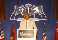 An unidentified man standing behind a podium giving a speech in the Centennial Student Ballroom, Mankato State University.