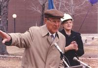 Unidentified man with brown hat speaking at the Memorial Library addition dedication; Mankato State University President Margaret Preska is shown standing to the right behind him; Mankato State University; 1990