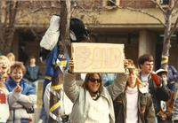 A student holding a sign that says BAND to support the band that will perform outside of the Centennial Student Union, Mankato State University