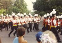 A marching band performing on the street during a summer parade in Mankato, MN