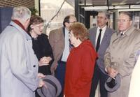 Margaret Preska (on left in black coat) speaking with an unidentified woman in a red coat at the Memorial Library addition dedication; Dr. Claire Faust (far right) standing with a hat in his hand; Three other unidentified men shown surrounding them having