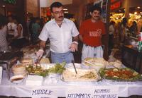 Men serving food at the Mankato State University International Festival, 04-06-1991.