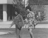 2 female students walking on the grass near the fountain, Memorial Library in the background, Mankato State University