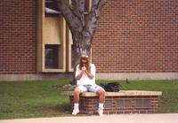 A student sitting outside the Performance Arts Center at Mankato State University.
