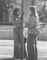2 female students visiting outside on the Mall; Armstrong Hall in the background, Mankato State University