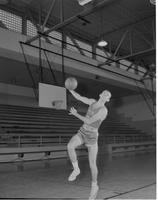 Mankato State College, male college student playing basketball, action shot, December 3, 1957.