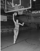 Mankato State College, male college student playing basketball, action shot on a basketball court.  December 16, 1957.