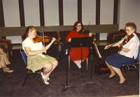 Three women playing the violin at Mankato State University, 1990-05-31.