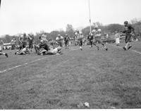 Football players in a play during a football game, Mankato State College, December 31,1957.